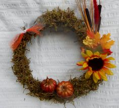 This 12 x 12 Grapevine wreath has been covered in moss to give it that Fall texture. The sunflower, colorfull leaves and pumpkins give it
