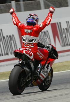 Loris Capirossi celebrates taking Ducati`s first ever MotoGP victory, at Catalunya.
