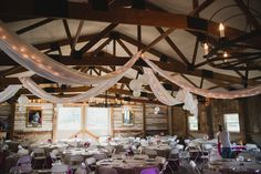 white lights, fabric, and lanterns are draped from wood rafters in a rustic barn for reception decor
