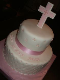 Beautiful baby girl baptism cake, with edible cross, covered in a white marshmallow fondant and little pearls all around.