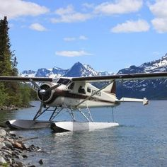 Float plane rests in the water with snow capped mountains behind after flying in to a remote Alaska location on an Ultimate Fly-in Trip.
