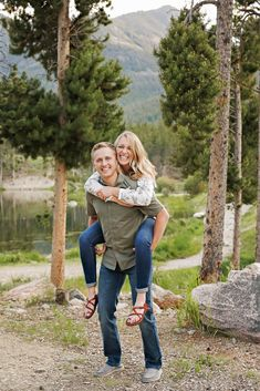 Summer Engagement Session - Red Lodge - Mountains - Trees - Sunset - Rocks - Lake - Water - Piggyback - Fiance - Engaged Couple - Green Shirt - Olive Shirt - White Floral Shirt - Jeans - Montana Wedding Photographer - Sara Nagel Photography Engagement Couple, Engagement Session, Engagement Photos, Olive Shirt, Red Lodge, Montana Wedding, Lake Water, How To Pose, Green Shirt
