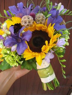 The bridal bouquet will be similar in shape and color with bold yellow sunflowers, white hydrangeas, purple dendrobium orchids, white anemones, scabiosa pods, white freesia and looped bear grass.  The bridesmaids would carry a smaller version of the bridal bouquet, and would have purple freesia and anemones in place of white.