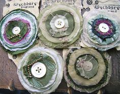 A new batch. Some of these have layers of synthetics that I've heat distressed over a candle flame - loads of fun! Fabric Brooch, Sari Fabric, Fabric Art, Sari Silk, Textile Jewelry, Fabric Jewelry, Jewellery, Felt Flowers, Fabric Flowers