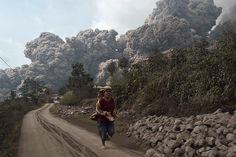 A villager runs as Mount Sinabung erupts at Sigarang-Garang village in Karo district, Indonesia's North Sumatra province, Saturday. Reuters