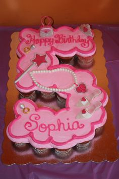 A cupcake cake for a princess' fifth birthday.  Decorations modeled after party supplies (shown in additional photo).  Cupcakes are strawberry with raspberry buttercream icing.  (I wasn't sure if the flavors would go well together, but they complemented each other very nicely.)  Decorations are all buttercream fondant.