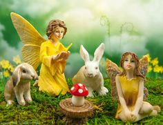Spring in the fairy garden.  Sunshine yellow fairies and miniature rabbits pose for an enchanted picture.