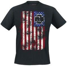 """Esta camiseta de Rammstein - Amerika muestra una versión alterada de la bandera americana algo sucia y con el logo de Rammstein entre las estrellas. En la espalda reza """"We're All Living In Amerika"""" en los colores tradicionales de Norteamérica, rojo, blanco y azul, con el rótulo de Rammstein bajo el dibujo."""