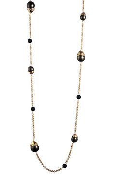 """Alexis Bittar. Smooth black onyx stones join a scattering of crystal-capped shell pearls in a golden necklace that can be worn long, layered or doubled.        Lobster clasp closure.      Approx. length: 52"""".      Shell/black onyx/Swarovski crystals/18k gold-plated base metal."""
