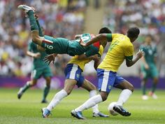 Mexico vs. Brazil soccer - Mexico's Oribe Peralta, middle, goes airborne in front of Brazil's Juan Jesus, right, as they pursue the ball during the men's soccer final at the 2012 Summer Olympics, Saturday, Aug. 11, 2012, in London. (AP Photo/Hussein Malla)