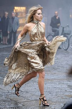 Turning up the drama: Suki showed off her incredible figure in a metallic animal print dress during the photoshoot forFerragamo in Florence