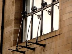 Wrought iron appendages to the north windows of These are not purely displays of ostentatious craftsmanship but did have a practical purpose: boards were laid on the horizontal brackets at the bottom, to allow access to. Charles Rennie Mackintosh, Glasgow School Of Art, Wall Lights, Ceiling Lights, Amazing Architecture, Wrought Iron, Candle Sconces, Art Nouveau, Chandelier