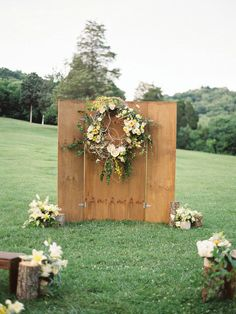 10 Unique Statement Walls for Your Wedding Decor | A rustic wooden backdrop is picture-perfect for your countryside nuptials. The placement of this gorgeous floral wreath gives it the final feminine touch. It is precisely what you need for your outdoor wedding decor.