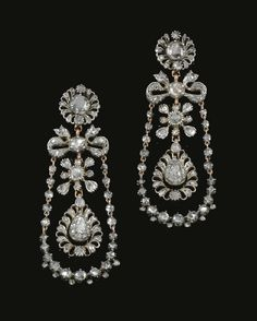 Pair of diamond pendent earrings circa 1800. Each of the stylized foliate and ribbon design, suspending a chain of rose diamonds in cut down collets and closed back settings, embellished with a swing set to the center with a pear shaped rose cut stone within surrounds of rose diamonds.