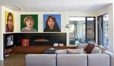 La sala de estar - AD España, © Virginia MacDonald Los retratos de los tres hijos de la familia presiden la sala de estar, que está comunicada con el jardín con enormes puertas correderas. Un retrato del perro les acompaña.