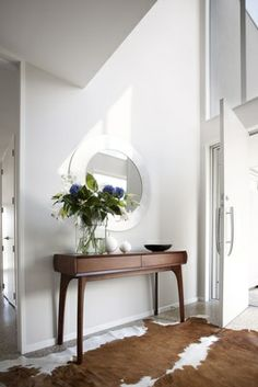 A modern entry foyer looks serene and gorgeous with a custom-designed hall table designed by Trinity Design and made by Freshwood Furniture, a striking round mirror, a cowhide rug and walls in Resene Half Tea walls. The interiors are also by Trinity Design. -