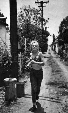 "MARILYN MONROE jogging through her neighborhood alley in 1951, before she was a superstar. Monroe made her film debut in 1947 providing the voice of an unseen telephone operator and appeared in numerous bit roles until finally landing her breakthrough role in ""Gentlemen Prefer Blondes"" (1953)."