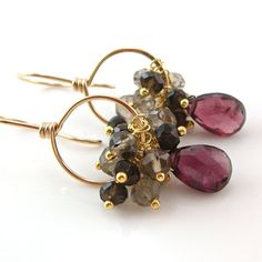 Garnet gemstone hoop earrings featuring gorgeous deep red garnet faceted briolettes surrounded with clusters of smoky quartz rondelles, all wire wrapped on hoops Ive handcrafted out of 14k gold filled wire. The garnets are simply beautiful, with wonderful rich red burgundy hues and plenty of