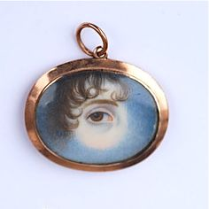 A gold pendant, c.1820, enclosing a watercolour-on-ivory miniature of a female eye set amid clouds, a symbol of mourning. (rowanandrowan.com)