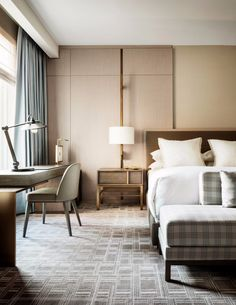 A modern hotel interior with a simple bedroom design that makes use of geometric patterns plus a desk and a few gilded details that accent the whole room.