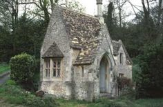 An English stone-built cottage house with steepled roofline.