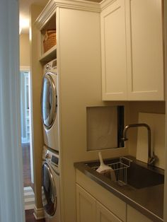 Stacked washer and dryer in custom built enclosure. Access hatch added for easing connection issues (cover panel removed in picture).