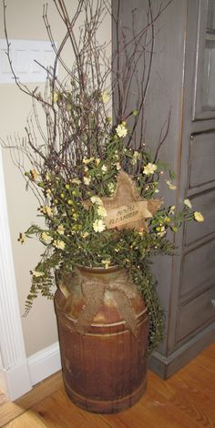 Large rusty milk can comes complete with tiny white rice lights,  twigs, greenery, delicate creamy yellow flowers, and a burlap star tucked in.  The lights really accent this arrangement and would brighten-up any spot in your home. The twigs almost reach the top of this six foot cabinet.  I did this piece to match any decor with it's subtle color combination.