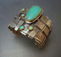 "Patricia McCleery - this cuff features a woven silver base, with 4 small Australian opals surrounding a blue green Peruvian Opal. The cuff is 2"" wide"
