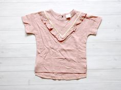 A+soft+pink+t+shirt+with+satin+v+and+ruffled+embellishment+on+the+chest.+The+back+has+a+peephole+closure.+It+has+a++cute+nautical/+preppy+look.
