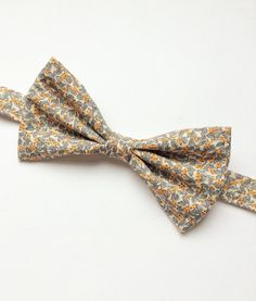 DESCRIPTION: Mens bow tie handmade using a gorgeous grey and orange floral cotton. FABRIC: 100% Cotton.  --------------------------------------------------------------------------------------------  DETAILS: • This bow tie is pre-tied • Attached to an adjustable strap fitting approx 15inch - 19inch neck size • Neatly packaged in a smart box with ribbon and tag attached • Lovingly handmade in the UK • Postage - UK delivery is sent first class with proof of postage, all other shipping is sent…