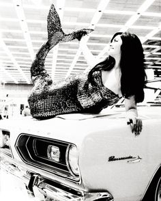 """1963 Detroit Auto Show, """"real life hood ornament"""" posing atop the 1964 Plymouth Barracuda."""