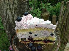 Eine Torte mit frischen oder eingefrorenen Heidelbeeren, einer Frischkäsefüllung und einem Frosting ummantelt. Die Krönung ist zerbröseltes Baiser.