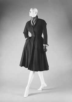 I love this coat, the collar of the coat is what really stands out. Dior was one of the designers to take standard pieces during the 50s and turn up the volume. The asymmetrical, almost sideways cowl like collar was quite nouveau for the time and many designers including Balenciaga modified this style. The way the coat is tailored is to fit to Dior's new look because of how small the waist line is.