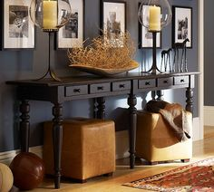 sofa table with 3 feet between it and the wall behind it and hang the pictures on the wall.Than the sofa table serves a purpose to put a drink on while sitting at the couch and gives the room depth.
