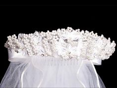 Lovely girls headpiece for First Communion has a beaded floral design with rhinestone accents. The back includes satin bows and a 24 inch veil.