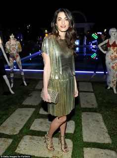 Eyes were on the Lebanon-native Amal: She opted for a gleaming silver frock for the evening