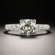 A bright and shining round brilliant-cut diamond, weighing 1.00 carat, sparkles solo from within a stately and sophisticated solitaire engagement ring, hand fabricated in platinum - circa 1930s. The vintage jewel is appointed with refined neoclassical design motifs and is finished throughout, and all around the ring shank, with expert hand engraving. Understated elegance par excellence. The diamond is accompanied by a GIA Diamond Grading Report stating: M color - VS2 clarity. Currently ring…