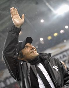 Juventus coach Antonio Conte salutes the crowd as his side carries him to his first ever Champions League Quarterfinal as a coach