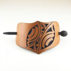 Carved leather barrette with wooden dowel