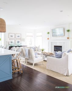 A spring living room and kitchen decorated in blue and white stripes. I love the linen sofas paired with the white spindle bobbin chairs! #springstyle #springdecor #livingroom