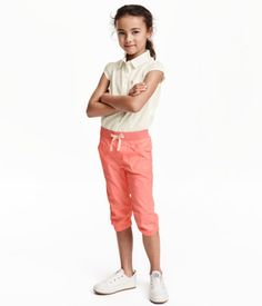 Pull-on pants in woven cotton fabric with elastication and a decorative drawstring at waist, mock fly, side and back pockets, and elasticized hems.