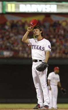 Texas Rangers starting pitcher Yu Darvish  of Japan takes off his cap during the seventh  inning of a baseball game against the Chicago White Sox Friday, July 27, 2012, in Arlington, Texas. (AP Photo/LM Otero)
