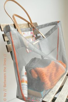 DIY Mesh Beach Bag Tutorial  How much do you like this see through DIY mesh beach bag with a leather handle? This type of hand bags are so much in fashion now days. Its netty fabric allows you to see what's inside the bag. And making it is just so damn easy lake making a cup of coffee.