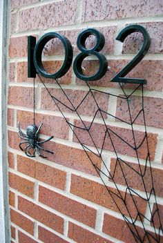 Easy DIY Halloween front door decoration - Yarn spiderweb and glitter-painted spider hanging from address numbers #spookyspaces
