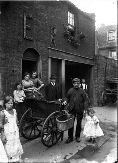 The cat's meat man pushed his barrow around East End streets selling cheap meat to families as pet food. Often horsemeat, it was unfit for human consumption and sometimes even too rotten for pets. The decoration on the house marks the coronation of Edward VII.