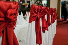 Chair covers with red bows adn detailing for wedding ceremony and reception