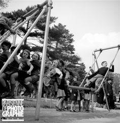 Enfants sur une balançoire, au Jardin d'Acclimatation. Paris, vers 1950. © Gaston Paris / Roger-Viollet
