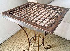 Antique Metal floor grate in it's new role as funky and chic side table.  Like