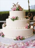 his small three-tiered chocolate cake covered in white buttercream is decorated with pink flowers.    From the wedding of Defne and Jonathan in Marblehead, Massachusetts.