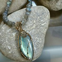 """Labradorite Pendant Necklace- Wirewrap Aqua Teardrop Labradorite Wirewrap Pendant, 50mm/2 """" long x 2mm/1"""" wide, flashing aqua, teal, lavender, with 3 mm Swarovski crystal at point. Necklace is created with beveled and donut shaped Labradorite beads, 18 """" long, flashing rainbows of blue. Wirewrap is created with antique Gold Filled wire. Beautiful for party or jeans. Leo Birthstone; Feldspar. Reputed to have healing and transformative powers. Inuit claim this stone fell from frozen fire of…"""